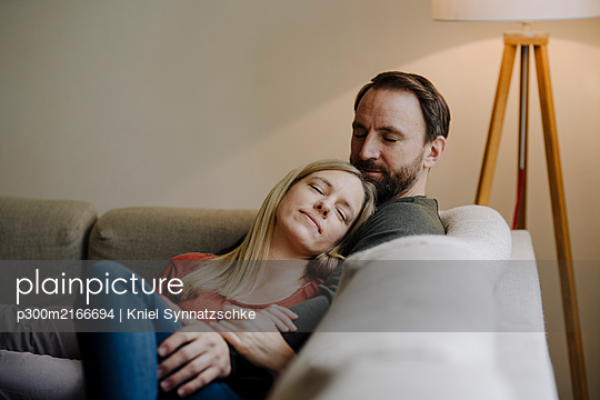 Couple sitting at home on couch, relaxing - p300m2166694 by Kniel Synnatzschke