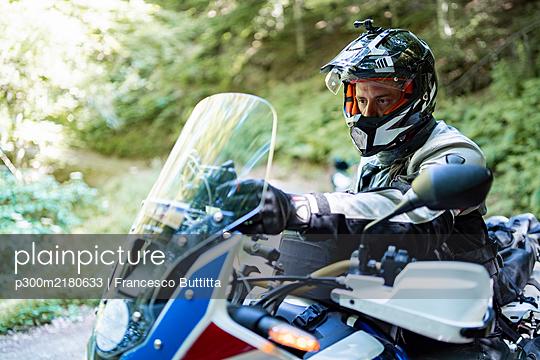 Motorcyclist on a trip adjusting sat nav - p300m2180633 by Francesco Buttitta