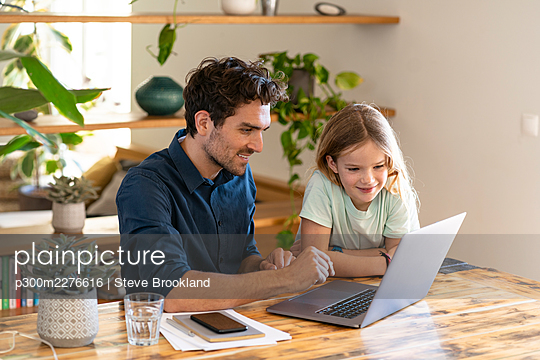 Happy father and daughter looking at laptop - p300m2276616 by Steve Brookland