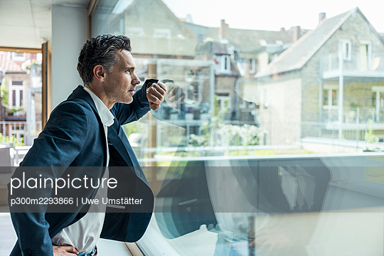 Businessman looking through window while standing in office - p300m2293866 by Uwe Umstätter