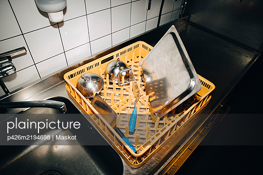 High angle view of basket with kitchen utensils on kitchen counter in cafe - p426m2194698 by Maskot