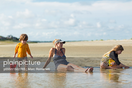 Caucasian families sitting in waves on the beach - p555m1522765 by Marc Romanelli
