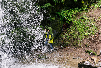 Water fall over teen with hoodie by ferns - p1166m2214707 by Cavan Images