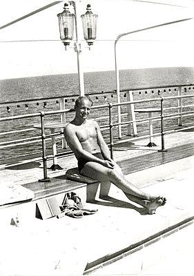Young man sunbathing on promenade - p1541m2116867 by Ruth Botzenhardt