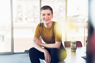 Portrait of smiling businesswoman sitting on desk in office - p300m2214143 by Uwe Umstätter