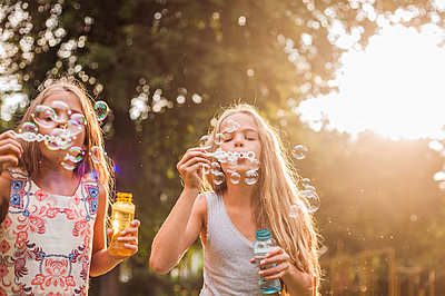 Girls blowing bubbles in park during sunset - p300m2239984 by LOUIS CHRISTIAN