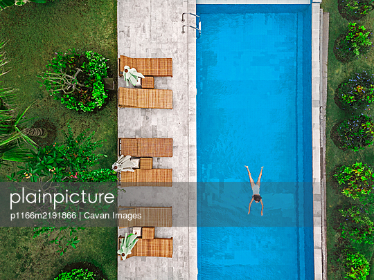 Aerial view of attractive woman floating over water at resort - p1166m2191866 by Cavan Images