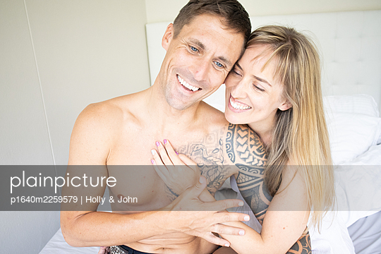 Couple in love sitting on bed, portrait - p1640m2259579 by Holly & John