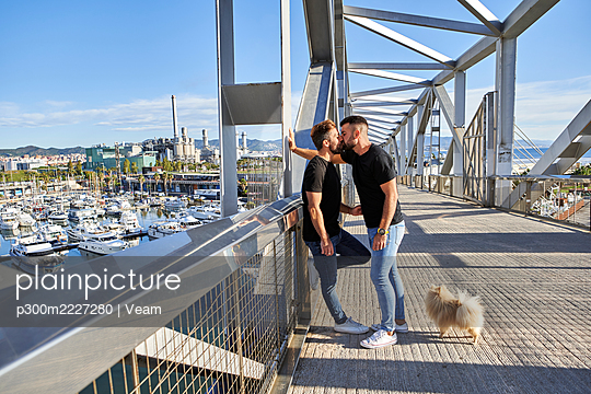 Affectionate gay couple kissing on footbridge during sunny day - p300m2227280 by Veam