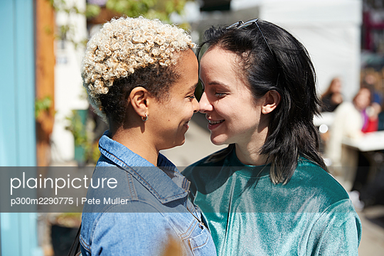 Lesbian couple smiling while looking at each other on sunny day - p300m2290775 by Pete Muller