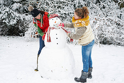 Mother and daughter making snowman - p1023m806033f by Paul Viant