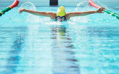 Swimmer racing in pool - p1023m923608f by Paul Bradbury