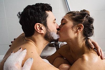 Junges Paar küsst sich leidenschaftlich in der Badewanne  - p1301m1424733 von Delia Baum