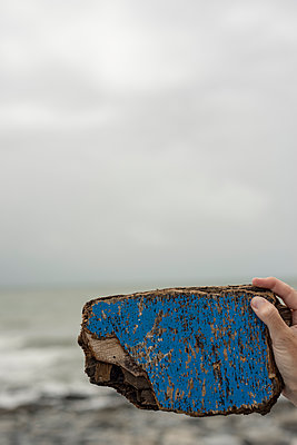Female hand holding a blue painted piece of driftwood before blurry beach and sea. - p1433m2014881 by Wolf Kettler
