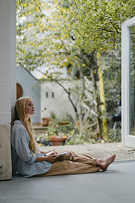 Young woman sitting at terrace door using tablet - p300m2170208 by Gustafsson