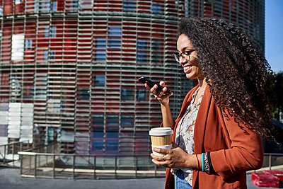 Smiling woman sending voicemail through smart phone while standing in city during sunny day - p300m2227292 by Veam