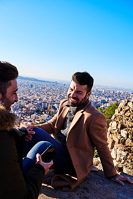 Happy gay couple talking while sitting on observation point against clear sky at Bunkers del Carmel, Barcelona, Spain - p300m2256693 by Veam