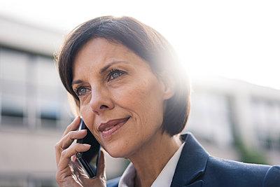 Mature businesswoman talking on smart phone outdoors - p300m2266645 by Joseffson