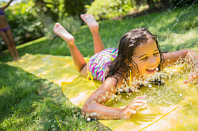 Mixed race girls playing on slip and slide in backyard - p555m1418766 by JGI/Jamie Grill