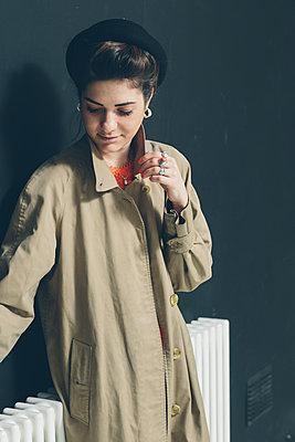 Female model in a beige rain-coat leaning against black wall  - p686m1124868 by Paul Tait