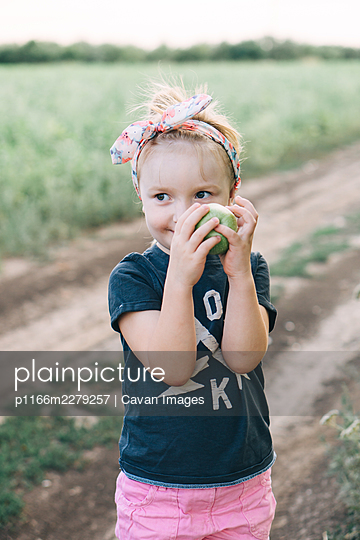 cute girl holds a green apple in her hands - p1166m2279257 by Cavan Images