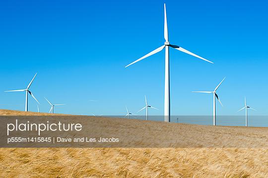 Wind turbines in field under blue sky