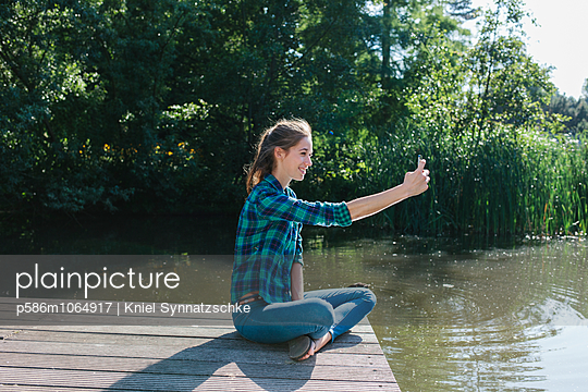 Young woman on the lakefront takes a selfie - p586m1064917 by Kniel Synnatzschke