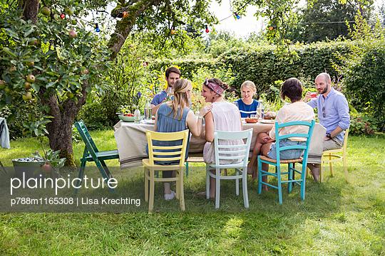 Freunde feiern eine Gartenparty - p788m1165308 von Lisa Krechting