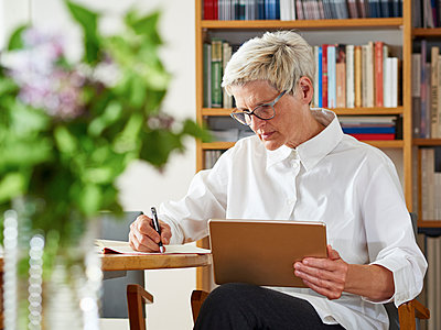 Senior woman with digital tablet writing down something - p300m1153773 by Dieter Schewig