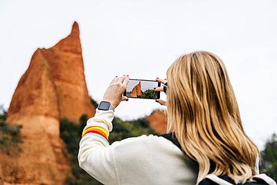 Female hiker photographing at Mina de Oro Romana, Las Medulas, Castile and Leon, Spain - p300m2170551 by Daniel González