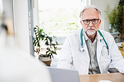 Male doctor with eyeglasses at desk - p300m2293791 by Uwe Umstätter