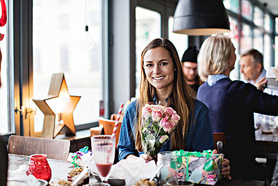 Portrait of smiling woman with gifts at dining table in restaurant - p426m1570196 by Maskot