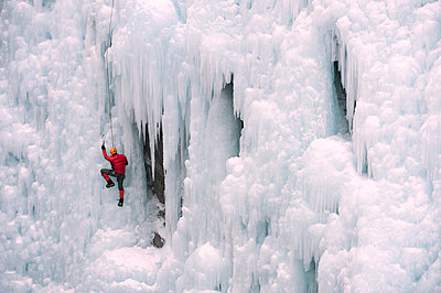 Caucasian man climbing ice wall - p555m1479333 by Pete Saloutos