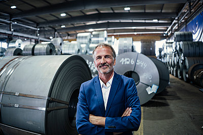 Smiling businessman with arms crossed standing at warehouse - p300m2299378 by Gustafsson