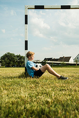 Germany, Mannheim, Teenage boy sitting on grass, leaning on goal - p300m948764f by Uwe Umstätter