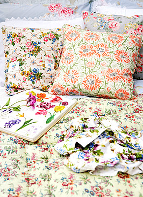 Floral cushions and gardening book in conservatory of Isle of Wight home;  UK - p349m920073 by Rachel Whiting