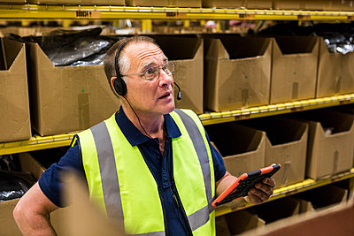 Senior male worker with digital tablet looking away while talking on headset against rack at distribution warehouse - p426m2018831 by Maskot