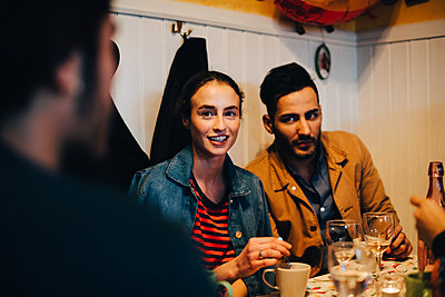 Young man and woman looking at male friend during dinner party at restaurant - p426m2046286 by Maskot