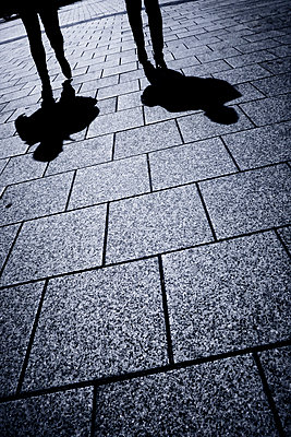 Shadows of couple walking along street - p597m1574263 by Tim Robinson