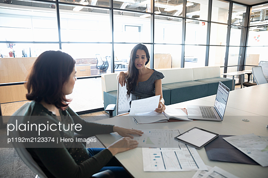 Businesswomen in meeting with documents in office - p1192m2123374 by Hero Images