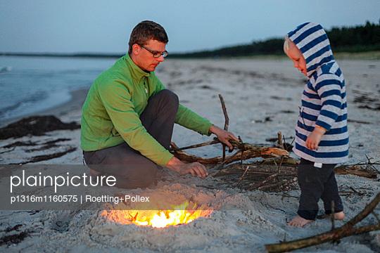 Vater und Sohn machen ein Feuer am Strand, Schaabe, Insel Rügen, Mecklenburg-Vorpommern, Deutschland - p1316m1160575 von Roetting+Pollex