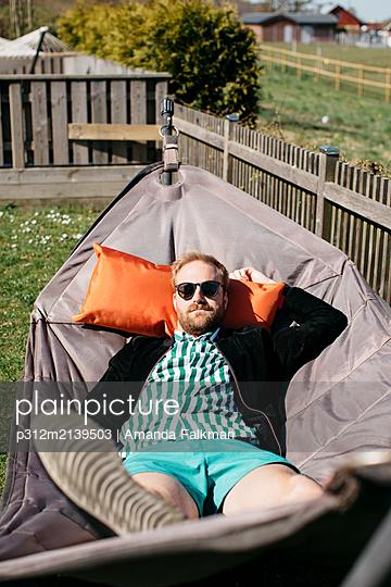 Man relaxing on hammock - p312m2139503 by Amanda Falkman