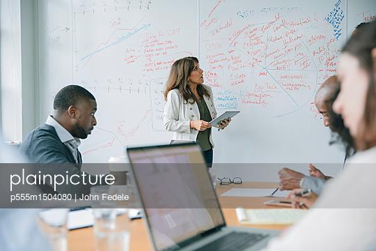 Businesswoman holding digital tablet near whiteboard in meeting - p555m1504080 by John Fedele