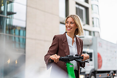 Happy young businesswoman with e-scooter in the city - p300m2143488 by Daniel Ingold