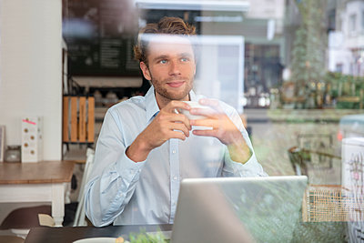 Young businessman with coffee cup and laptop in a cafe - p300m2155614 by Robijn Page