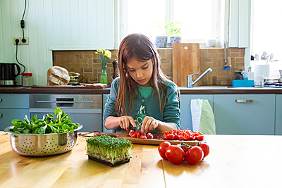 Girl cutting tomatoes on chopping board in kitchen - p300m2189259 by Larissa Veronesi