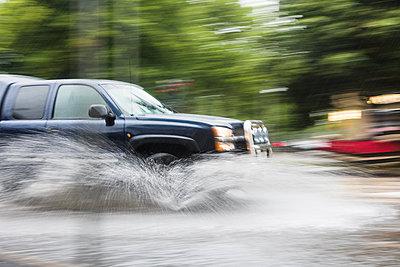 Car splashing water on road - p312m1103762f by Mikael Svensson
