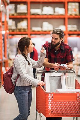 Couple discussing while standing with shopping cart in hardware store - p426m1407345 by Maskot