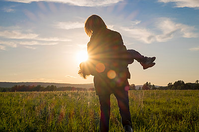 Woman carrying son in field at sunset - p555m1304062 by Aliyev Alexei Sergeevich