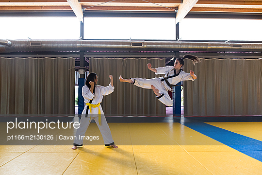 Side view of two young women in white kimonos attacking and fighting. - p1166m2130126 by Cavan Images